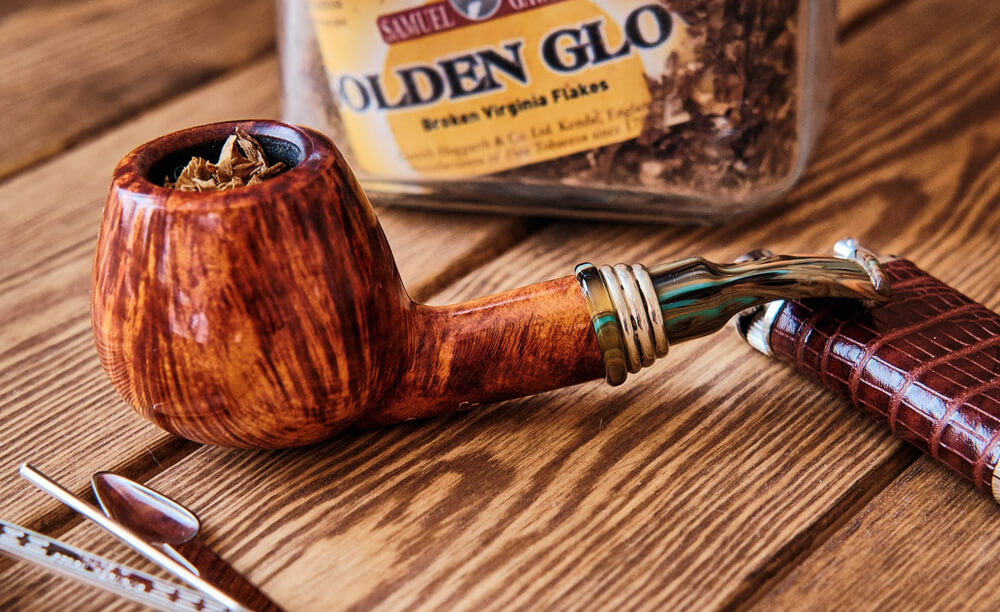 Briarová fajka naplnená tabakom a fajkový príbor na drevenom stole