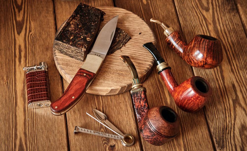 Briarové fajky, fajkový príbor a fajkový tabak s nožom položený na stole