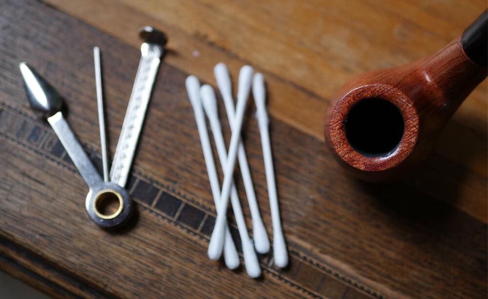 Fajka na tabak, čistiace tyčinky a fajkový príbor na drevenom stole