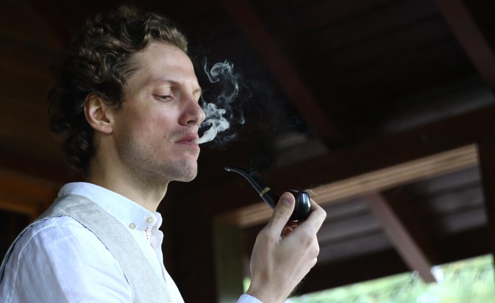 Mladý muž fajčí fajku