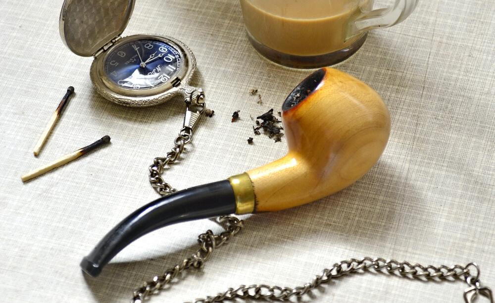 Fajka zo svetlého dreva naplnená už spáleným tabakom položená na stole, vreckové hodinky a káva