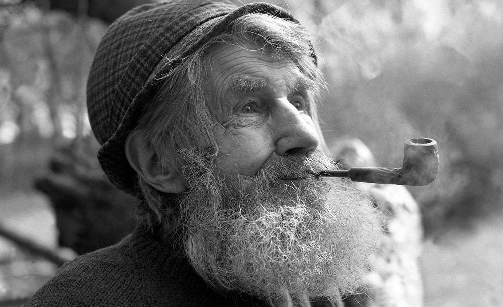 starý bradatý pán v baretke fajčí fajku na tabak